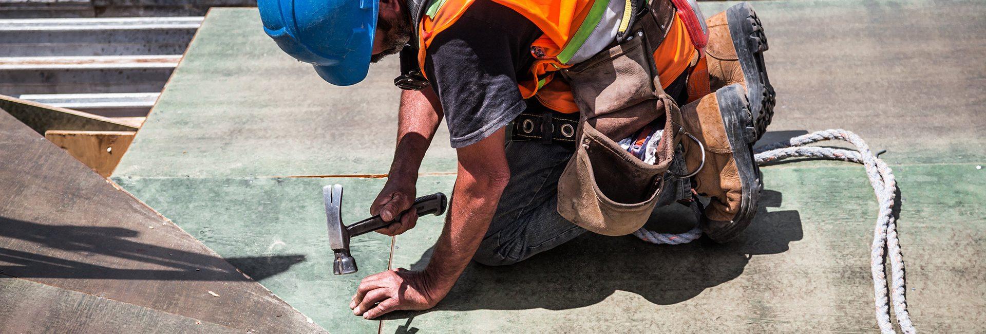 man-wearing-blue-hard-hat-using-hammer-resize